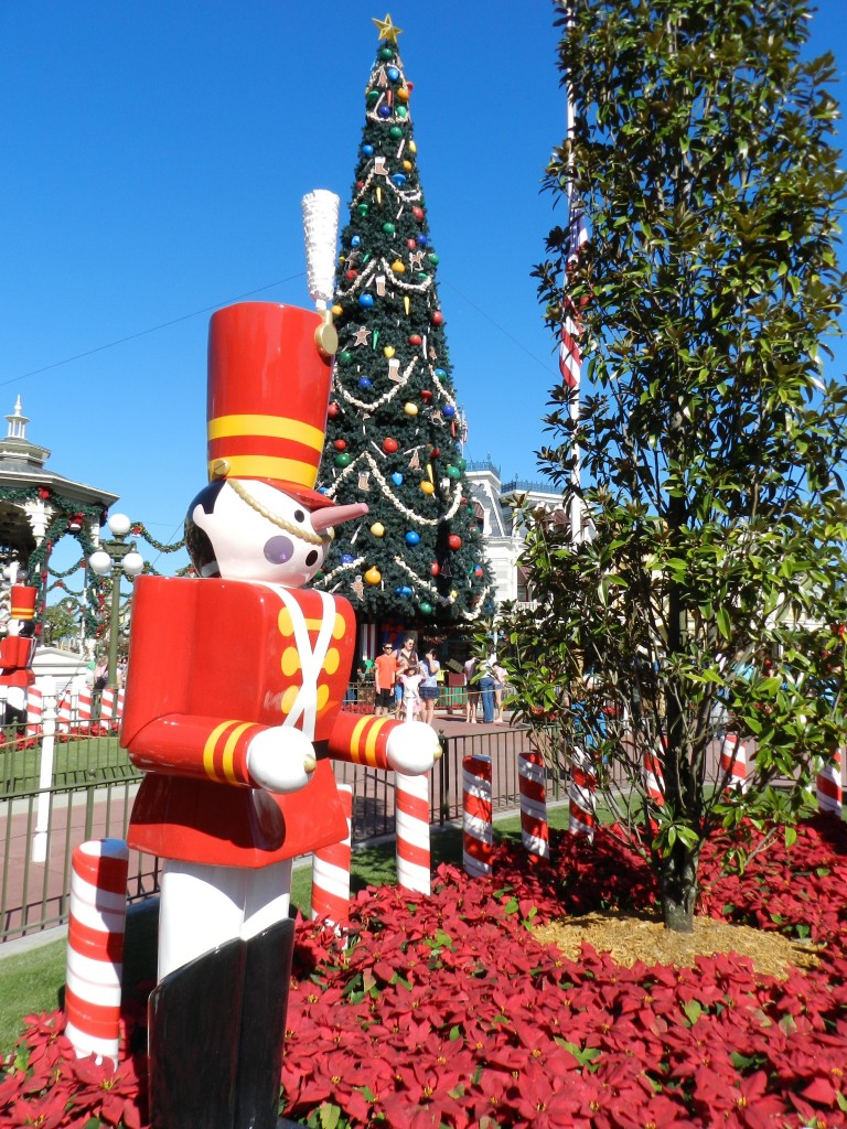 Mickey's Very Merry Christmas Party is a great event to put on your Disney World solo itinerary! Red, white, and yellow toy soldier in front of Christmas tree.