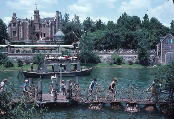 Visitors crossing barrel bridge to Tom Sawyer Island attraction near Haunted Mansion at the Magic Kingdom - Orlando, Florida.