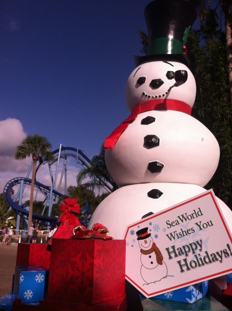 Happy Holidays from SeaWorld Orlando with Cheery Snowman in the Florida Sun with Manta roller coaster in the background.