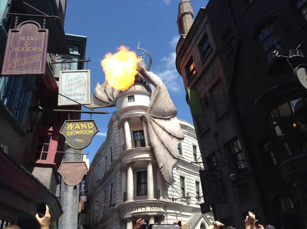 """Diagon Alley: Fantastic Beasts and stuffed animals on shelves and fire-breathing dragon on Gringotts"