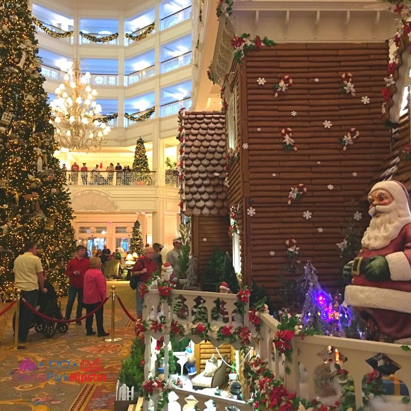 Disney Grand Floridian Gingerbread House Display with Santa on the Porch and Christmas Tree in the Background