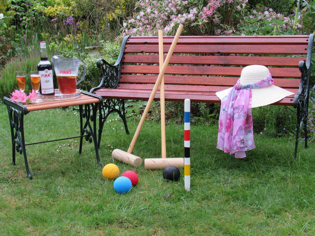 Pimm's cup next to croquet on bench
