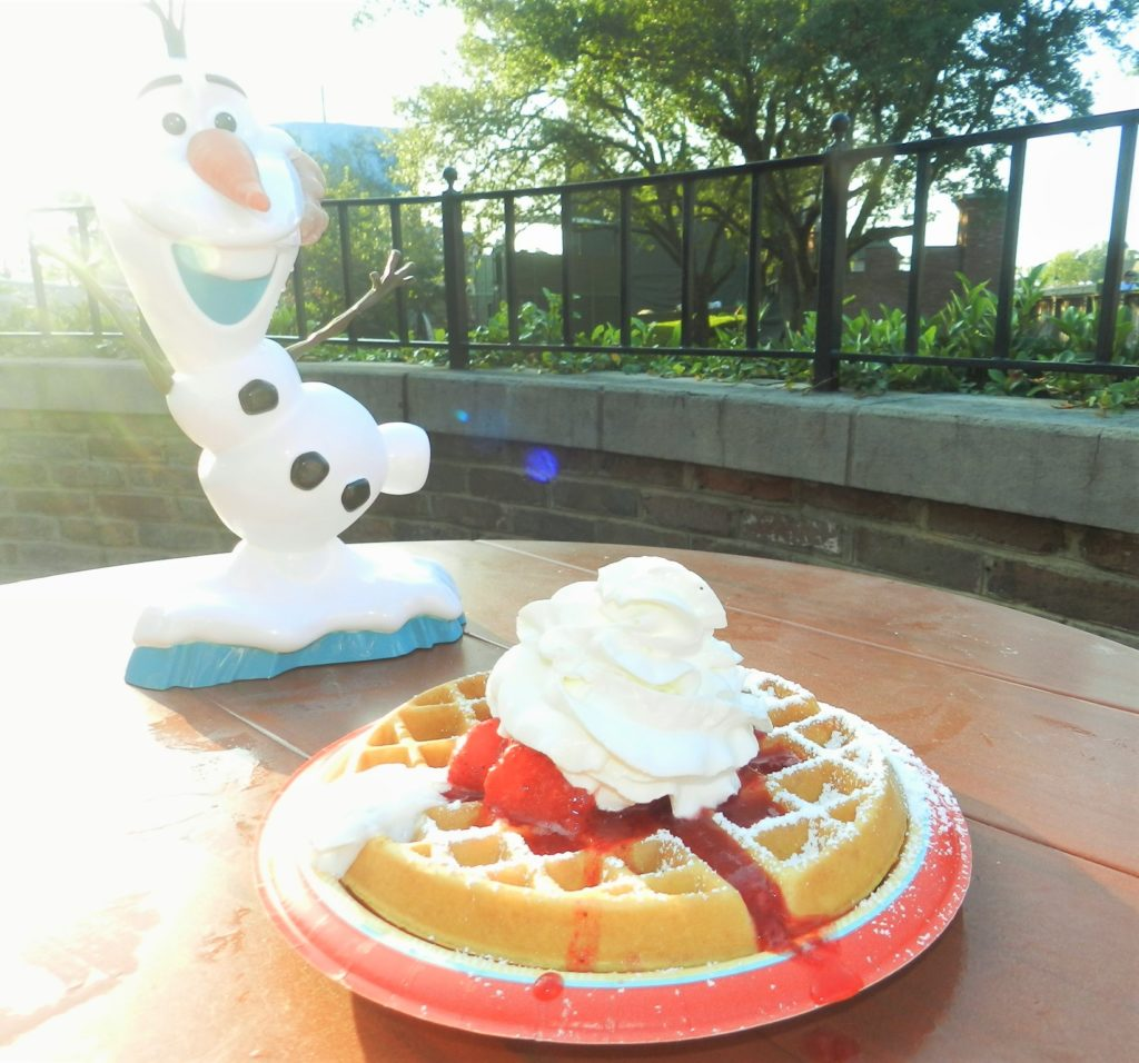 Disney Dining Waffles at Sleepy Hallow with fluffy waffle topped with creamy red strawberries and thick whip cream.