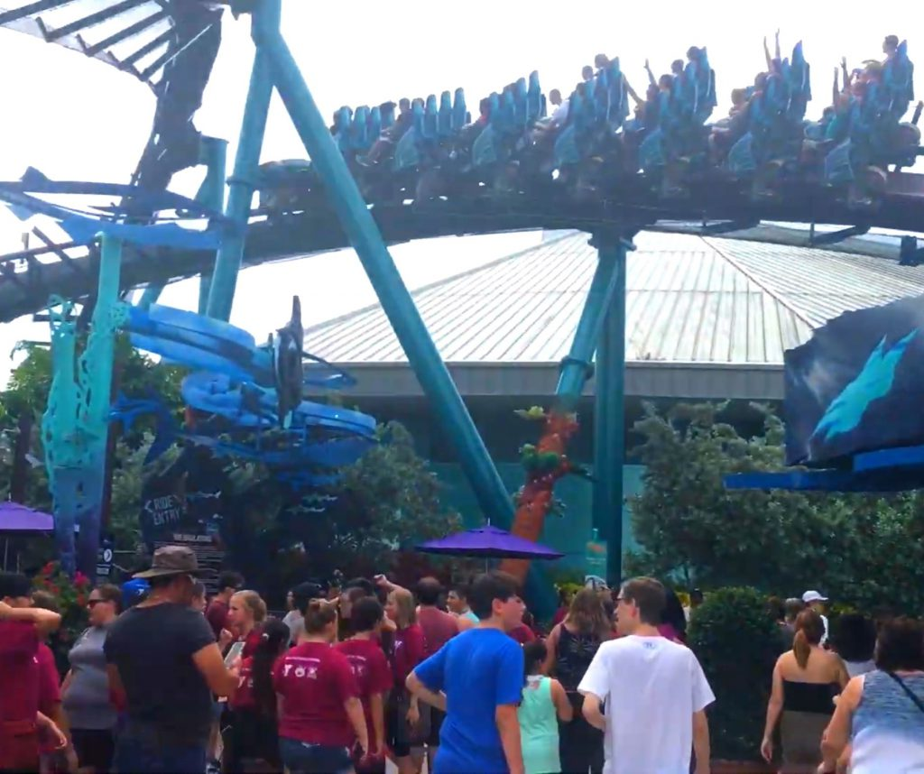 Mako at SeaWorld Orlando Speeding by people near the front gate Purple and Deep Blue Roller Coaster