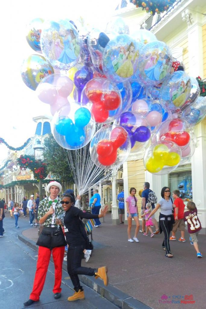 Christmas at Disney Parks with Disney Cast Member Holding Balloons in Magic Kingdom