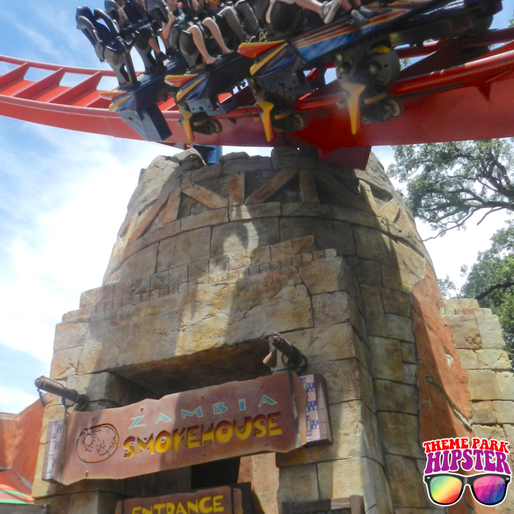 Zambia Smokehouse Busch Gardens with Sheikra roller coaster flying by.