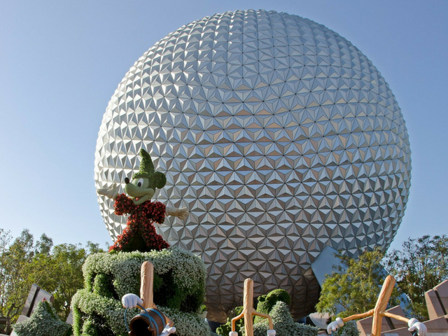 Mickey Mouse in front of Spaceship Earth Globe at Epcot.  A perfect photo spot for your Disney solo trip.