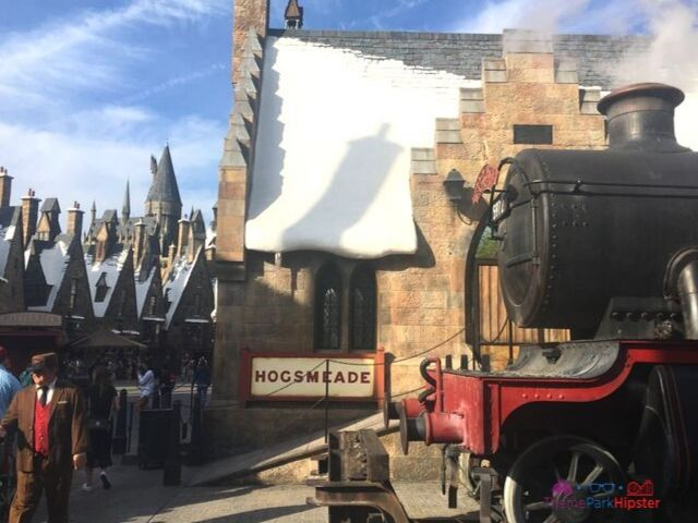 Hogsmeade at Universal with steam coming from engine and guests walking around.