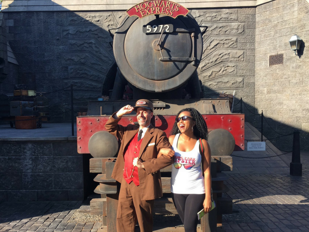 What to pack for universal orlando resort. Standing with Hogwarts Express Conductor in front of red train. Hogsmeade Universal.