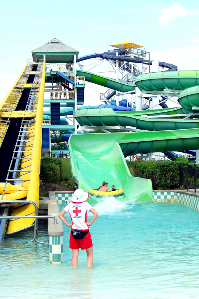 First timer water park tips. Lifeguard in front of green water slide.