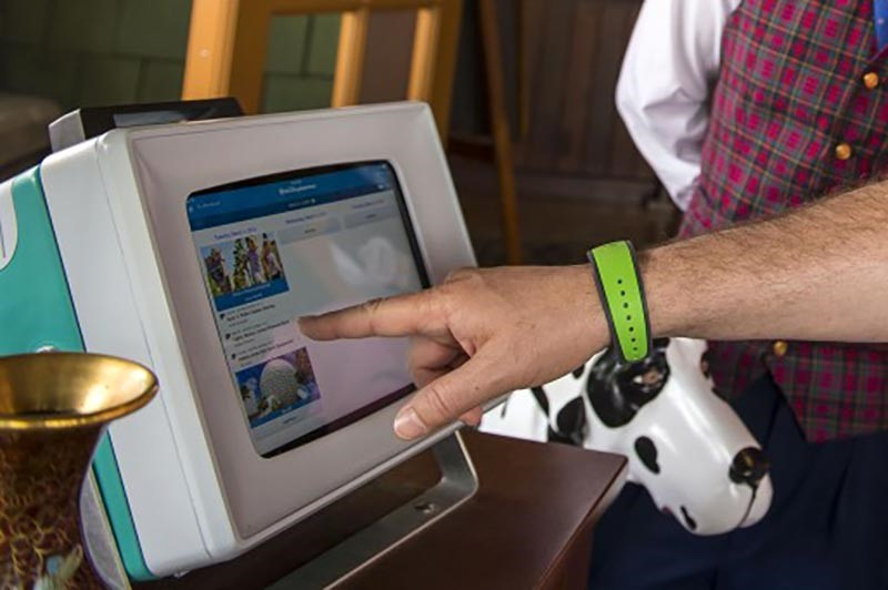 Disney MagicBand 2 with Cast Member selecting FastPasses.