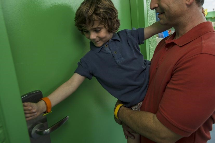 MagicBands are the new Disney World Resort hotel key! Use them to unlock your hotel room door. Dad and son unlocking room with band.