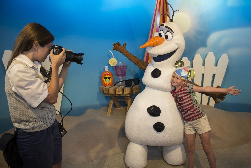Use your MagicBand to save your Photopass pictures to your account.  Cast Member taking photo of guest with Frozen character.