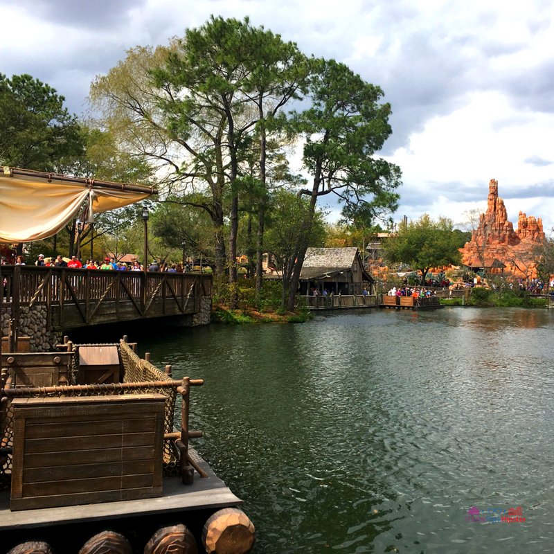 Tom Sawyer Island at Magic Kingdom with raft on water and Big Thunder Mountain Railroad in the background. Disney Secrets.
