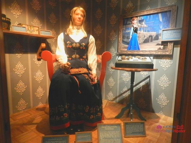 Norway Pavilion at Epcot Woman Sitting in Traditional Chair and Garb Next to Frozen Animation Image
