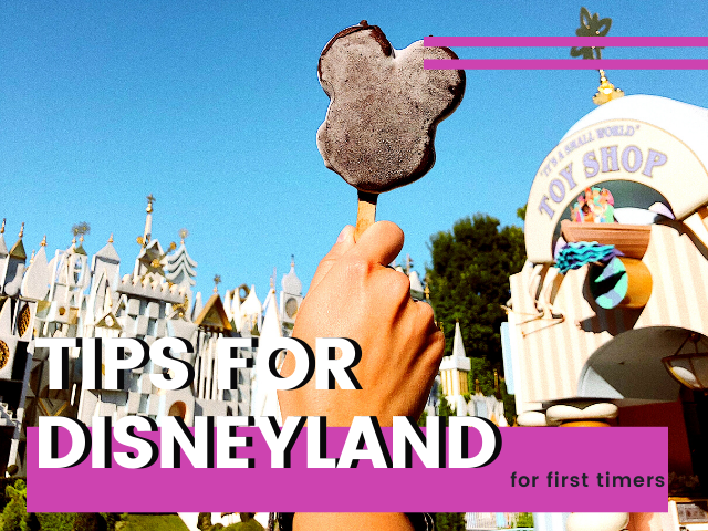 Disneyland tips for first timers with person holding a frozen Mickey Mouse Ear bar in front of it's a small world ride at Disneyland.