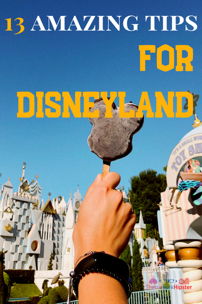 13 Amazing Tips for Disneyland with delicious chocolate Mickey Mouse Ice cream bar with it's a small world ride in the background on a sunny California day.