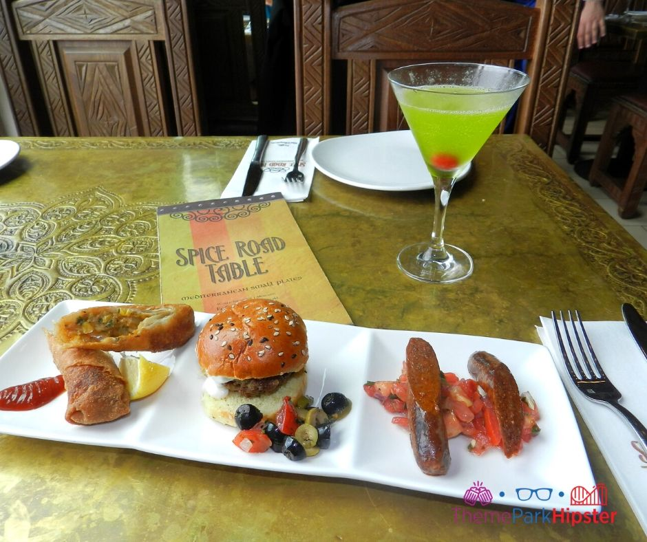 Spice Road Table at Epcot Lamb Sausage and Lamb Slider on White Plate with Green Martini