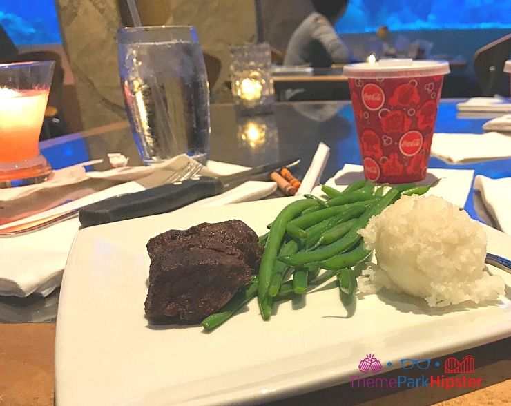 Living Seas restaurant at Epcot Rainbow prime steak with green beans and rice overlooking aquarium