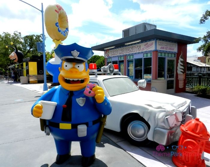 Chief Wiggum from the Simpsons eating a big pink donut in front of Lard Lad Donuts