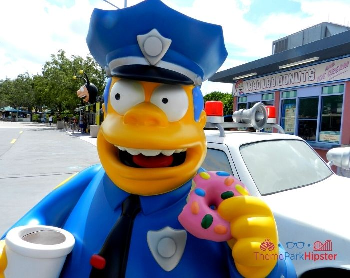 Chief Wiggum from the Simpsons eating a big pink donut