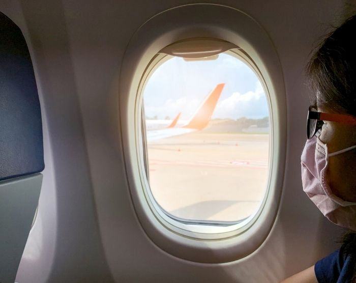 Jetlag with woman on airplane with mask