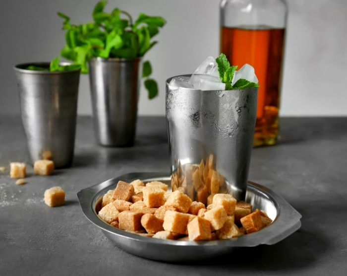 Mint Julep Disneyland ingredients with sugar cubes mint and brown liquor on table
